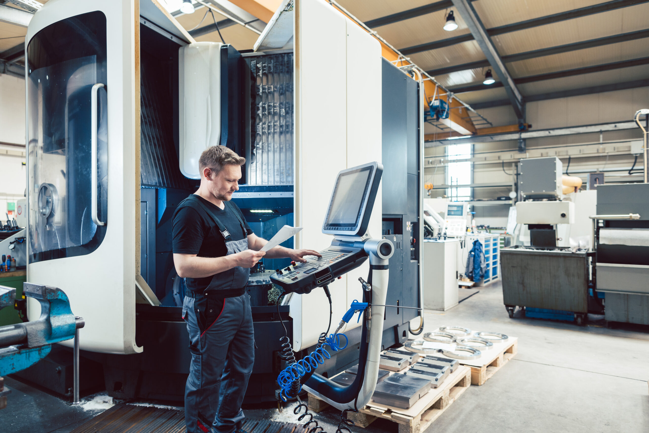 Worker in metal industry operating a modern cnc machine